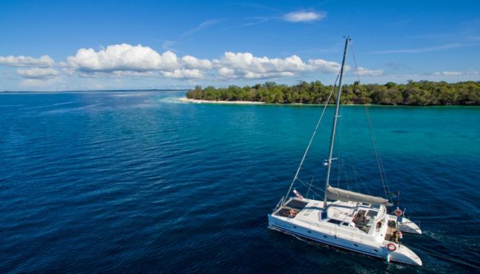 Catamaran yacht cruising past Mesali Island in Pemba, Tanzania.